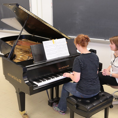 Students practice piano skills in 十大靠谱网赌网址's piano lab with Assistant Professor of Music, Margaret Young.